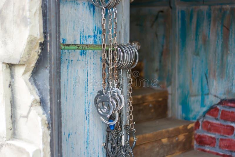 垂悬在入口前面的墙壁上的手铐对土牢 图库摄影