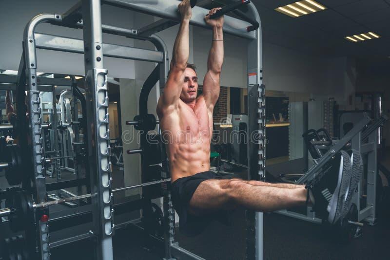 垂悬在单杠的健身人执行腿培养,在健身房 图库摄影