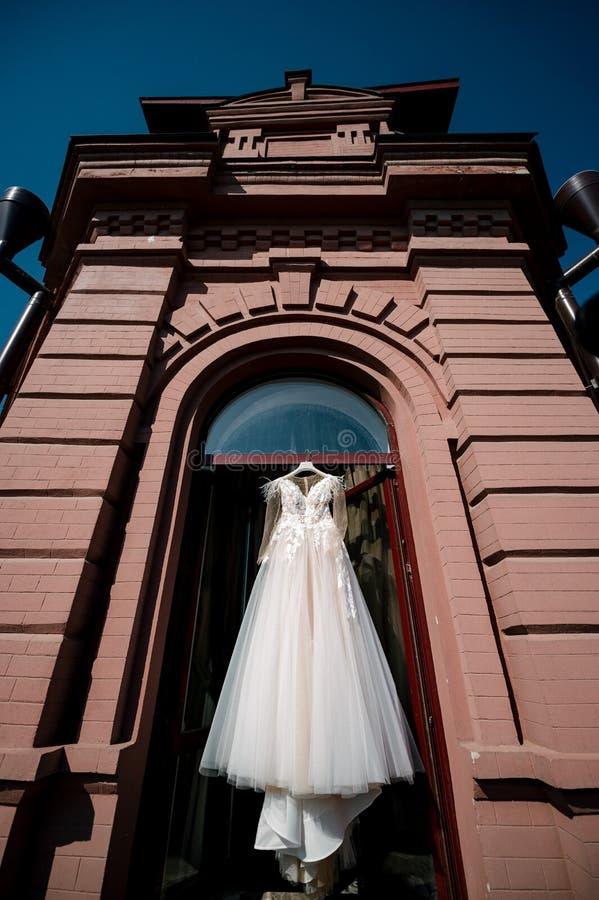 垂悬在卧室的白色婚纱 白色新娘礼服 免版税库存照片