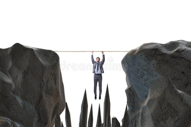 垂悬在危险概念的绳索的商人 库存图片