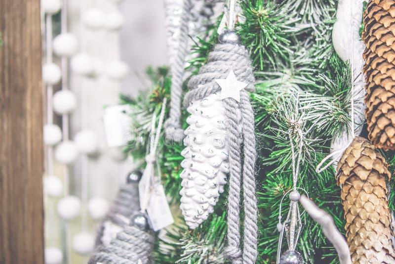 垂悬在圣诞树的装饰白色圣诞节快乐新年的玩具杉木锥体 库存照片