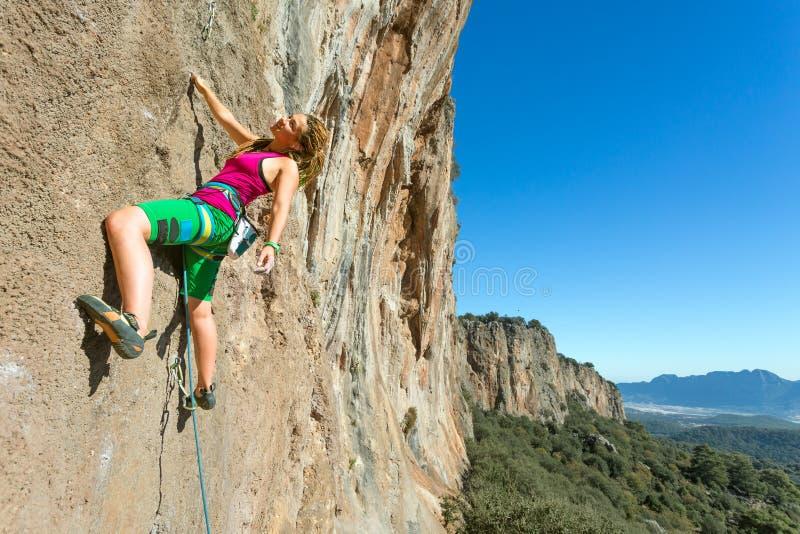垂悬在垂直的墙壁上的青年女性攀岩运动员 免版税库存照片