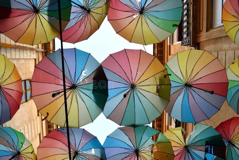 垂悬在城市街道上的五颜六色的伞 免版税库存照片