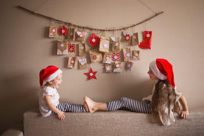 垂悬在墙壁上的出现日历 孩子的小礼物惊奇 当地精戏剧打扮的两个姐妹 库存照片
