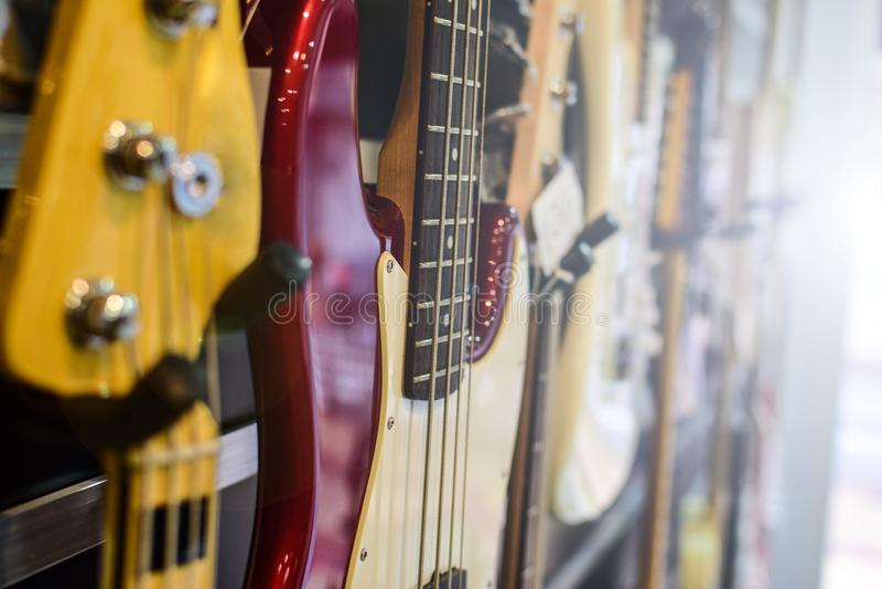 垂悬在墙壁上的吉他和低音吉他在商店 回到光 免版税库存照片