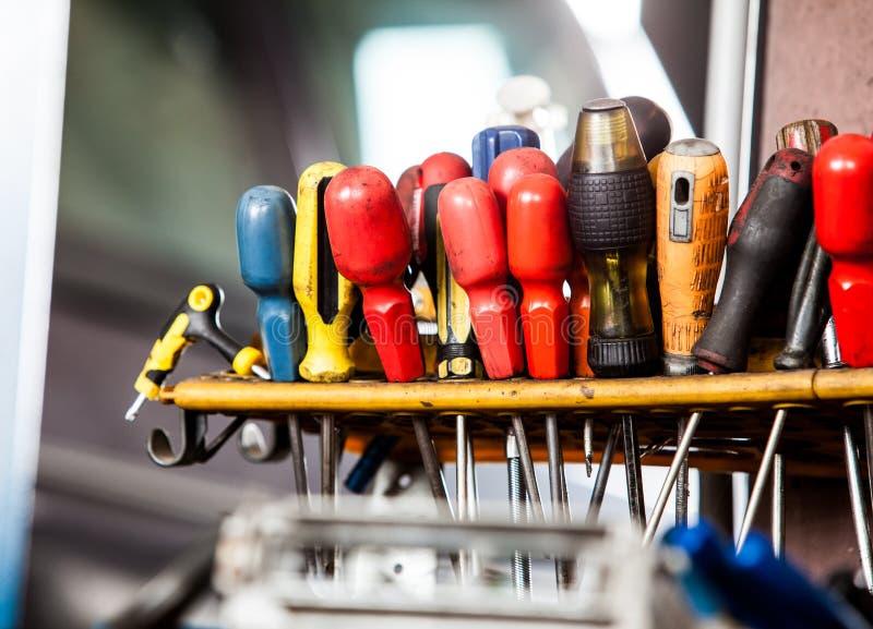 垂悬在墙壁上的工具的分类。在技工车库汽车服务的螺丝刀 库存图片
