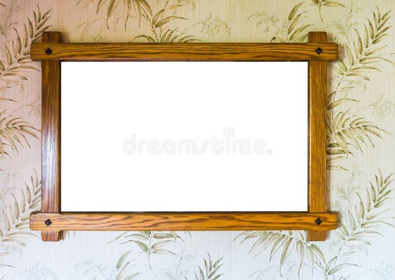 垂悬在墙壁上的空的棕色木相框有装饰的墙纸背景 免版税库存图片