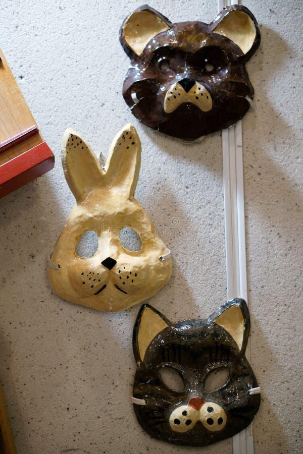 垂悬在墙壁上的老葡萄酒狂欢节面具 野兔、熊和猫 免版税库存照片