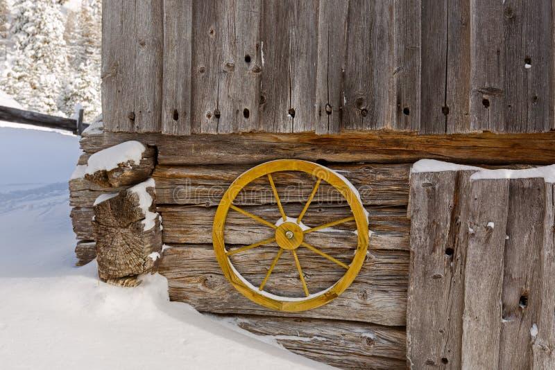 垂悬在墙壁上的老黄色马车车轮装饰土气木 免版税库存图片
