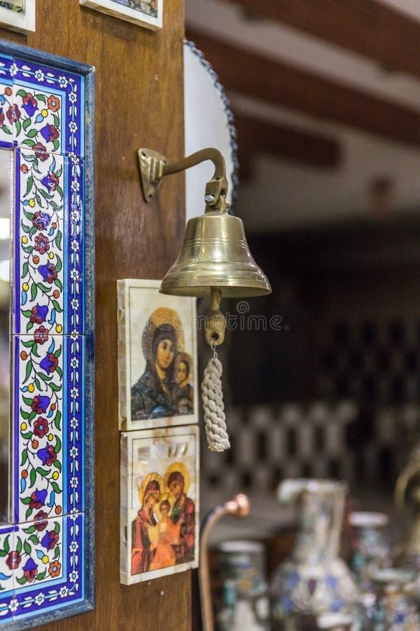 垂悬在墙壁上的铜响铃在路旁商店在Kerak市附近在约旦 库存图片