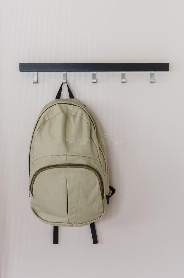 垂悬在墙壁上的绿色旅行背包 库存图片