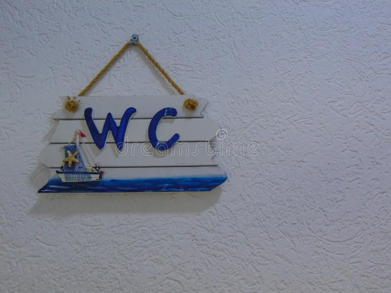 垂悬在墙壁上的WC标志 免版税库存图片