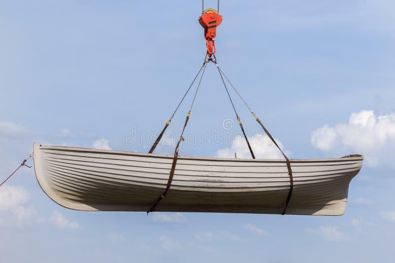 垂悬在天空蔚蓝背景的一个起重机勾子的划艇 免版税库存图片