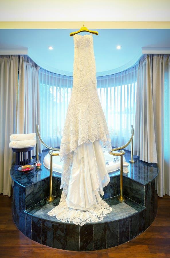 垂悬在天花板的婚礼礼服在豪华屋子里 免版税库存图片