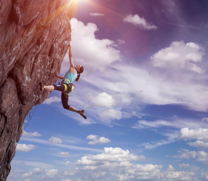 垂悬在她的手上的登山人 免版税图库摄影