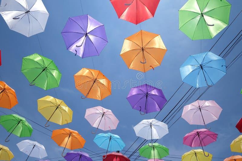 垂悬在导线的顶视图多彩多姿的伞反对天空蔚蓝白色云彩 库存图片