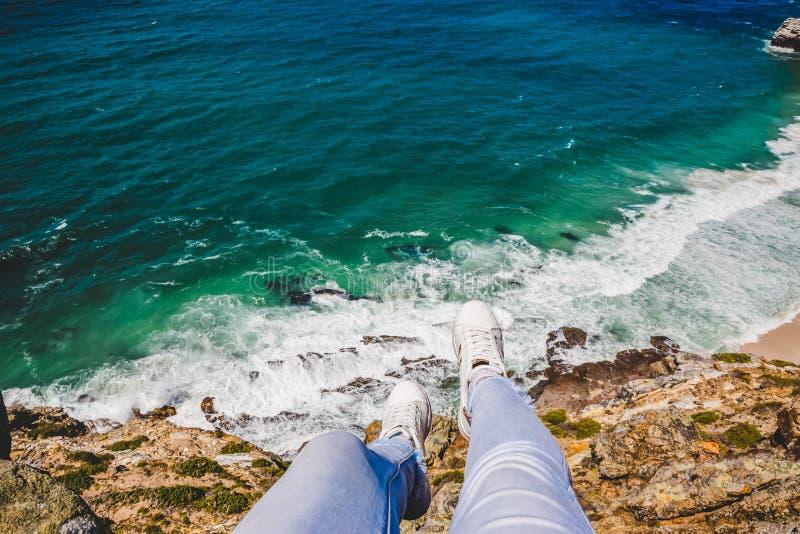 垂悬在峭壁的边缘的腿 库存照片