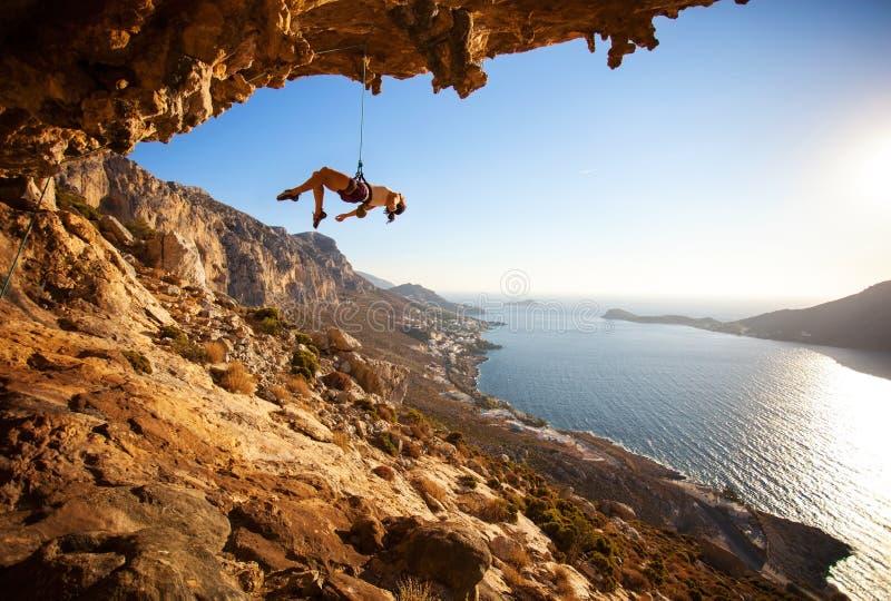 垂悬在峭壁的绳索的女性攀岩运动员 库存图片