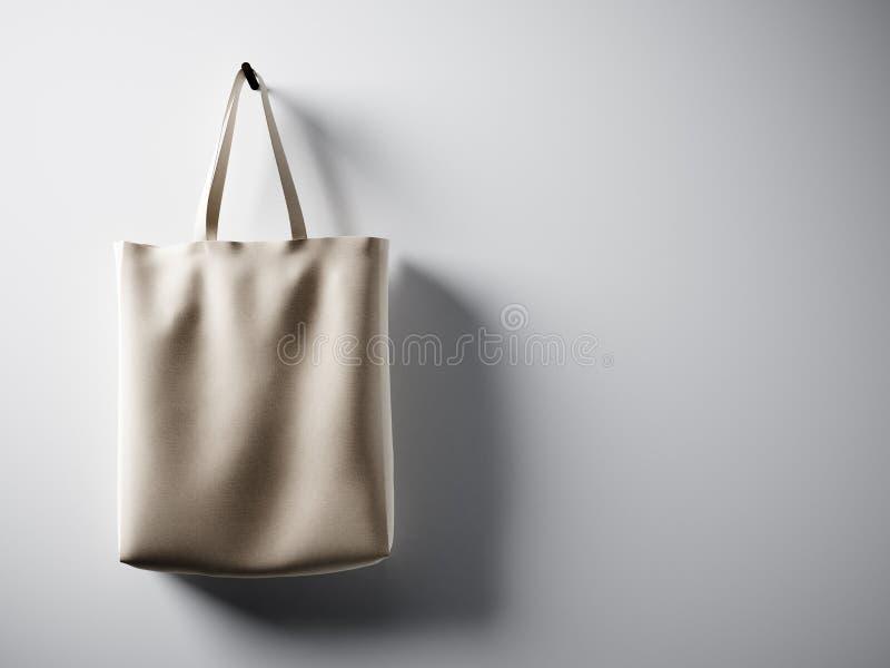 垂悬在左边的照片黑棉纺织品袋子 空的白色墙壁背景 高度详细的纹理,企业混乱的空间 免版税库存图片