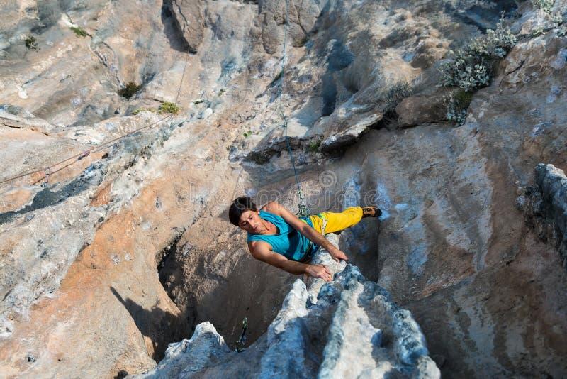 垂悬在异常的形状的岩石的成熟男性极端登山人 免版税图库摄影