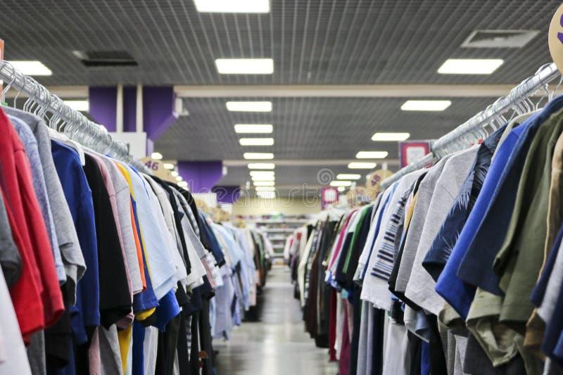 垂悬在挂衣架的两行的被编织的T恤杉在被弄脏的商店 在黑星期五的前夕 免版税库存图片