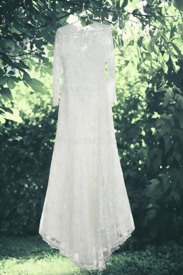 垂悬在挂衣架的婚姻的典雅的鞋带婚姻的白色礼服在树下 免版税库存图片