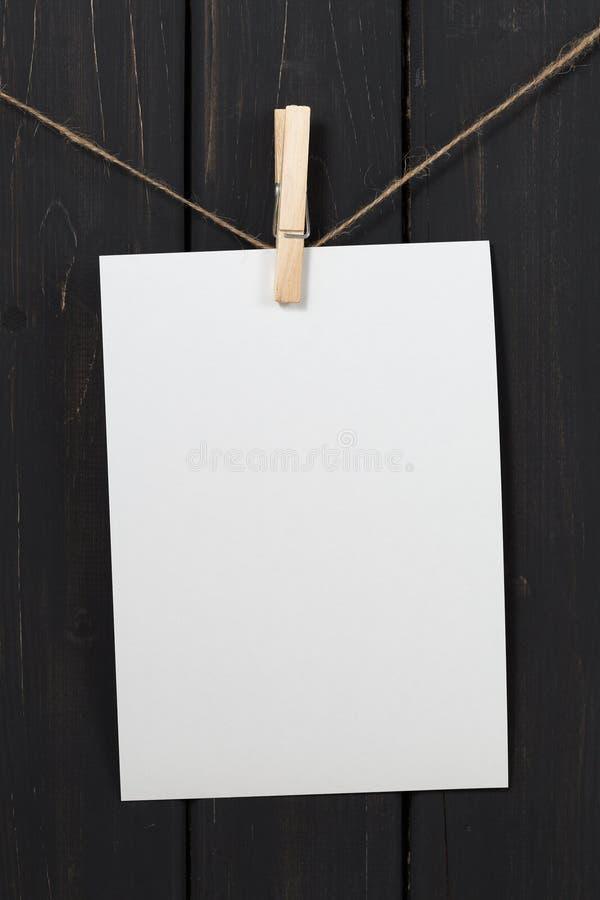 垂悬在晒衣夹的空白的白皮书卡片 免版税库存照片