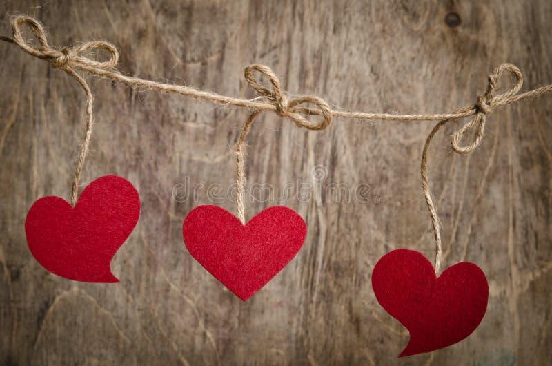 垂悬在晒衣绳的三红色织品心脏 库存照片