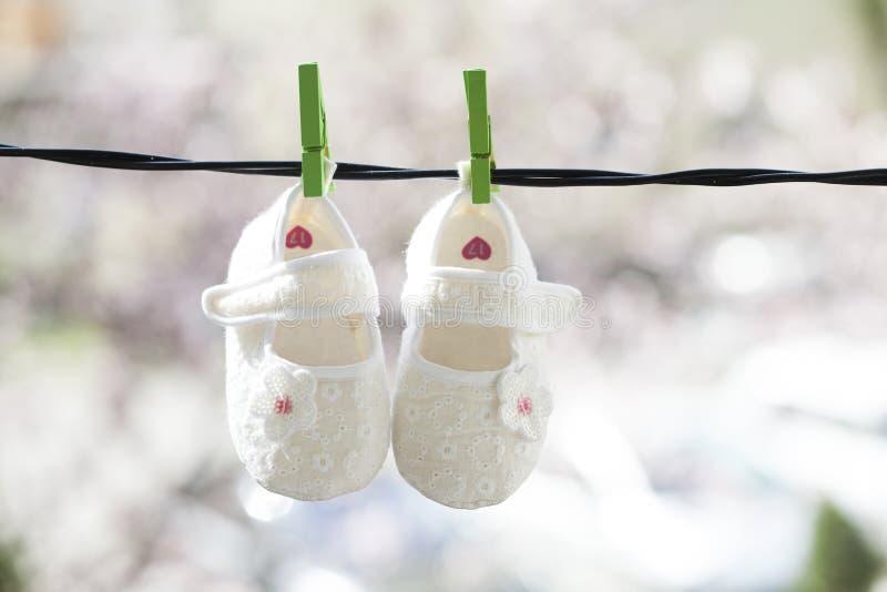 垂悬在晒衣绳的童鞋 免版税图库摄影