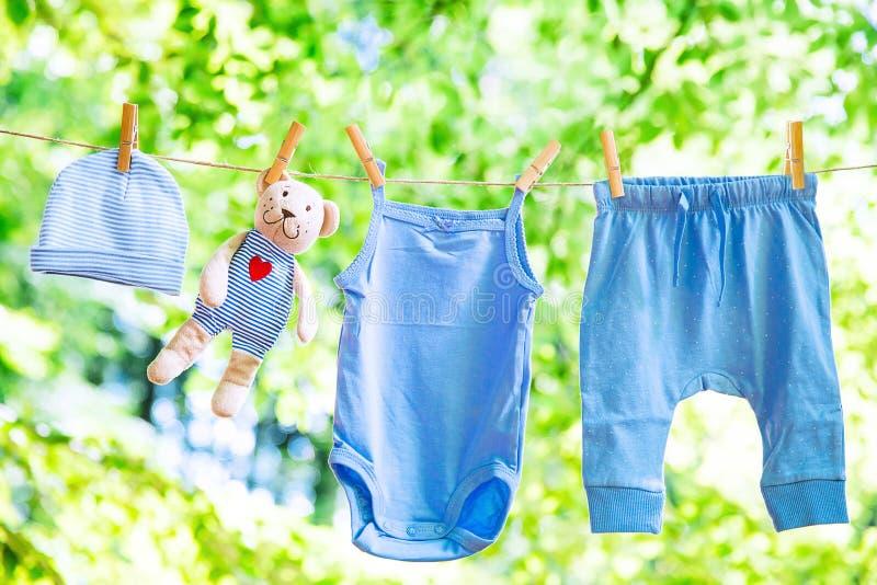 垂悬在晒衣绳的婴孩衣裳 免版税库存图片