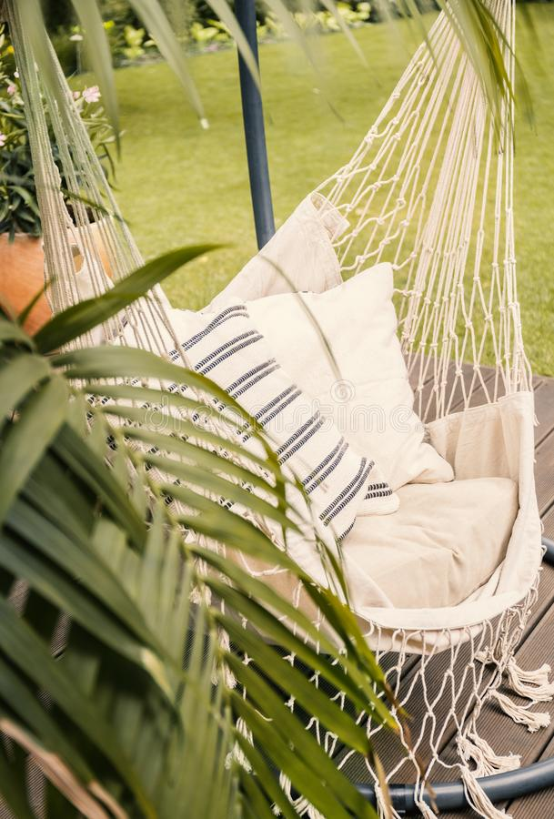 垂悬在有棕榈的一个晴朗的庭院里的boho吊床的特写镜头 库存图片