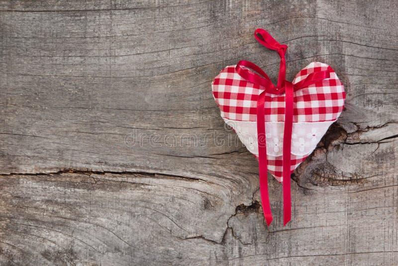 垂悬在木背景f的红色/白色方格的心脏形状 免版税库存图片