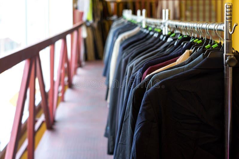 垂悬在机架的夹克、衣服和衬衣 免版税库存照片