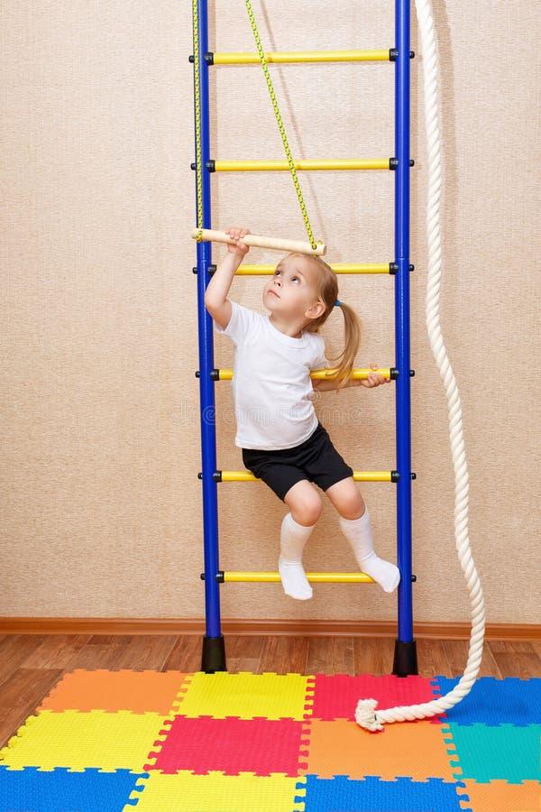 垂悬在标志横线的小女孩 库存图片