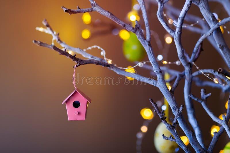 垂悬在树枝的小装饰嵌套箱室内与在背景的温暖的bokeh 免版税库存照片
