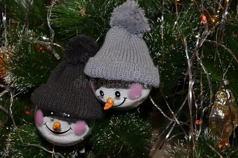 垂悬在树的圣诞节玩具 在被编织的帽子的两个雪人 图库摄影
