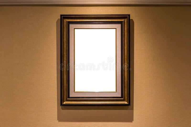 垂悬在棕色墙壁内部的空白的豪华照片框架 库存照片