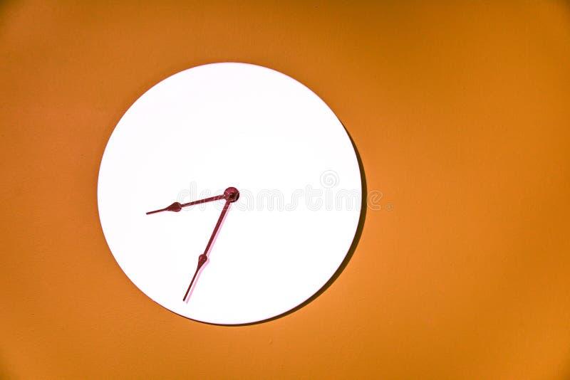 垂悬在橙色墙壁上的经典壁钟 免版税库存照片