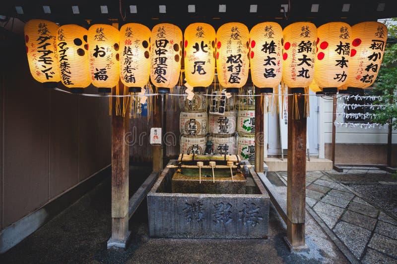 垂悬在水洗净液亭子的日文报纸灯笼在西龟Tenmangu寺庙,京都,日本 免版税库存照片