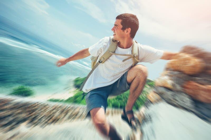 垂悬在海洋上的年轻勇敢的人 免版税图库摄影