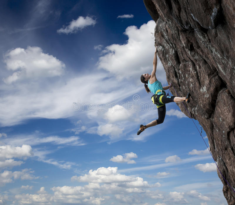 垂悬在深渊的女性攀岩运动员 免版税库存图片