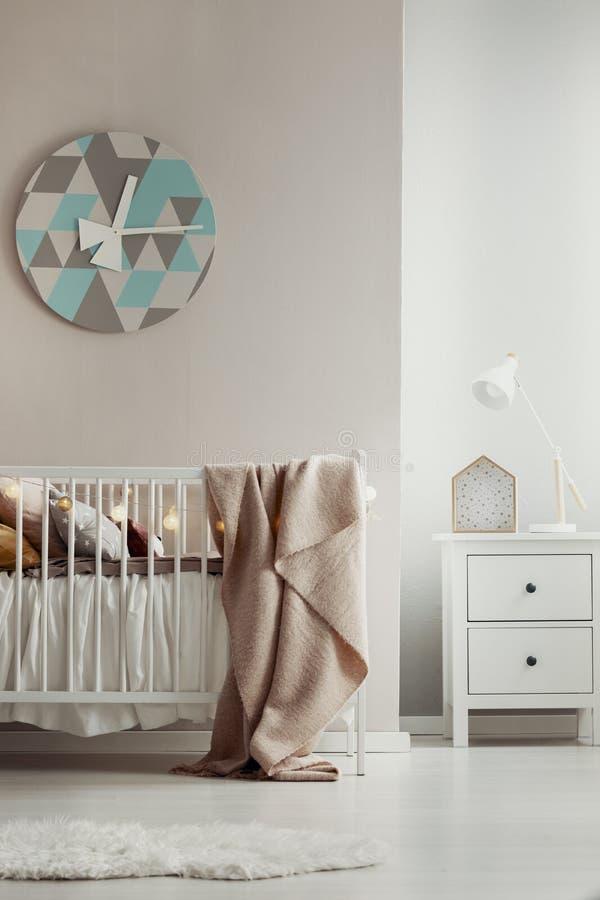 垂悬在温暖的婴孩室内部的米黄墙壁上的现代,几何时钟与白色小儿床 r 库存照片