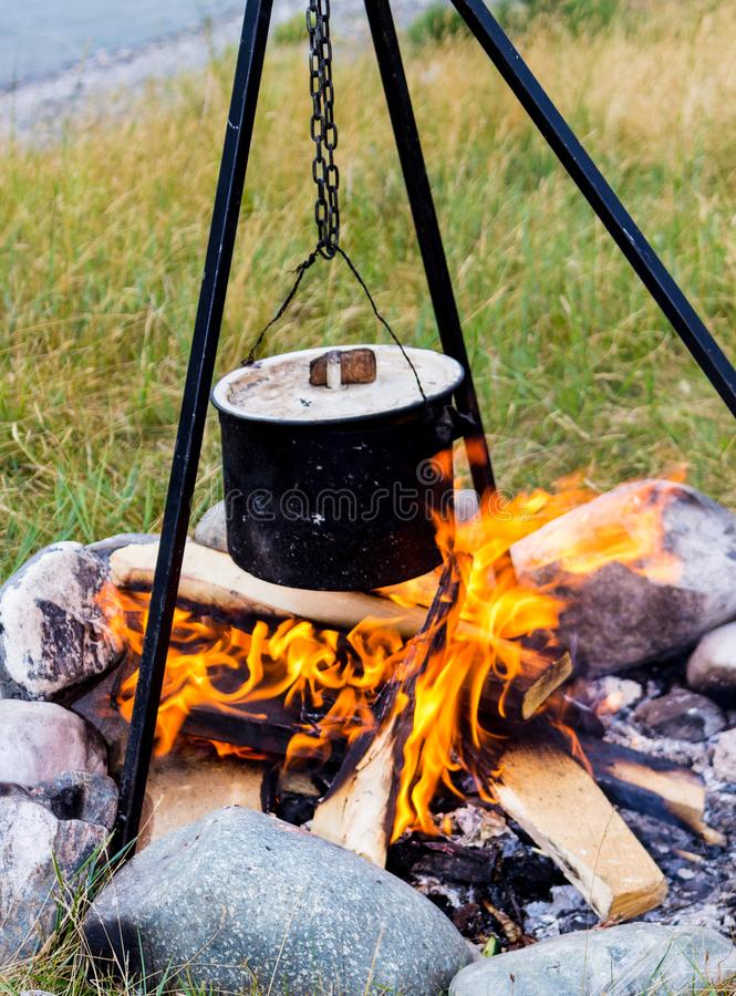 垂悬在火的平底深锅 免版税库存图片