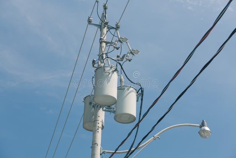 垂悬在灯柱的电子变压器反对深蓝天空 免版税库存照片