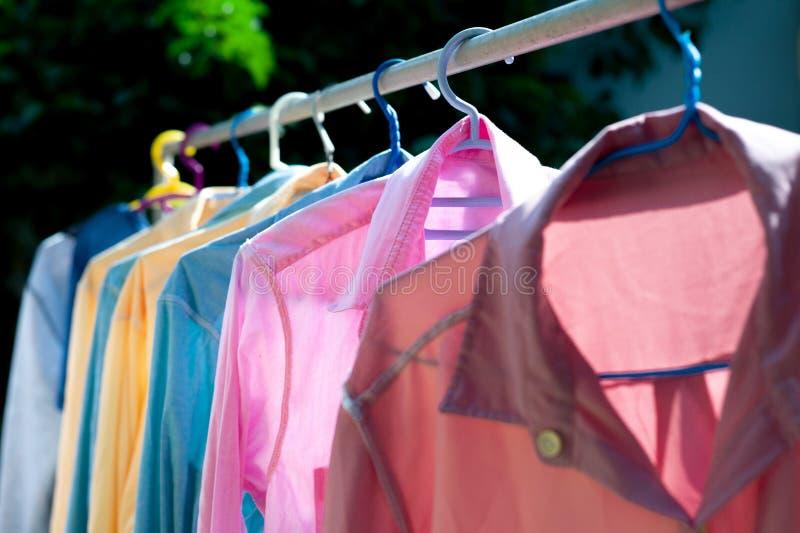垂悬在烘干的钢晒衣绳的五颜六色的湿衣裳由太阳热  免版税库存图片