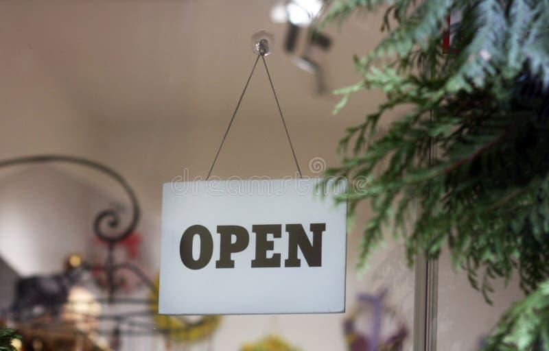 垂悬在玻璃门的开放标志 免版税库存图片