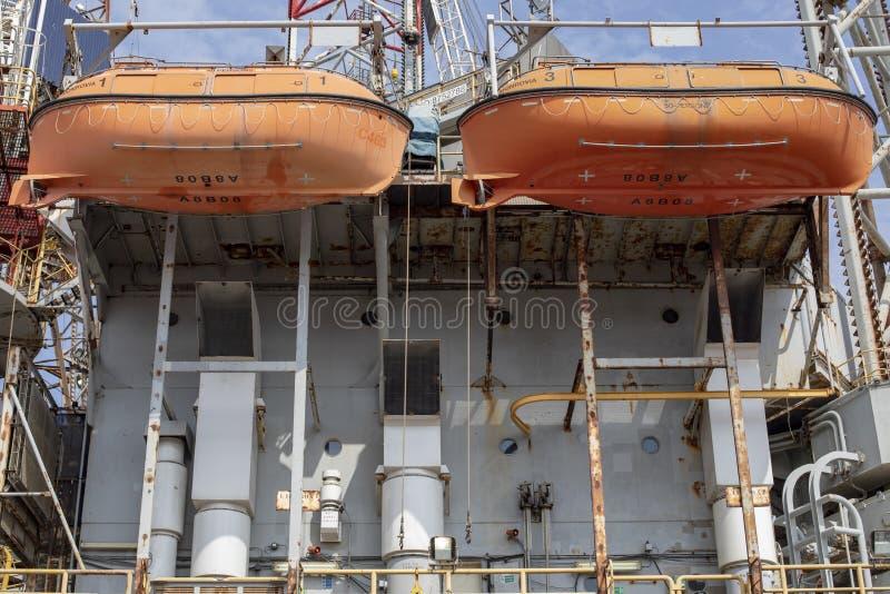 垂悬在生锈的集装箱船的两艘橙色救生艇 图库摄影