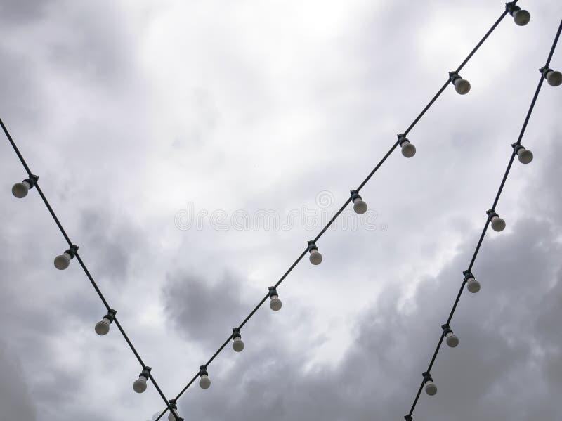 垂悬在电缆的装饰电灯泡行反对黑暗的多云天空 免版税库存图片
