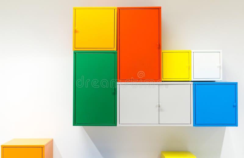 垂悬在白色墙壁上的五颜六色的金属内阁 免版税库存照片