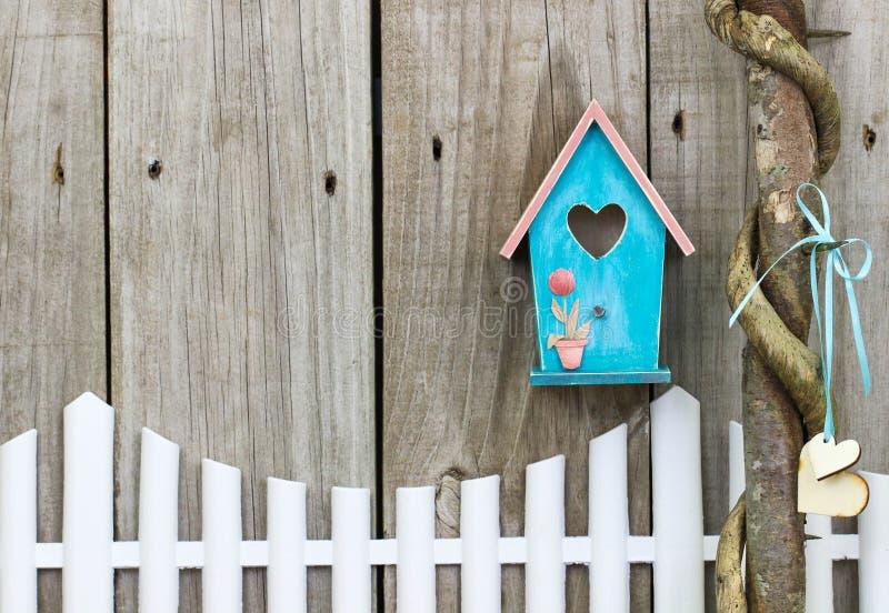 垂悬在白色尖桩篱栅的小野鸭蓝色鸟舍 免版税库存图片